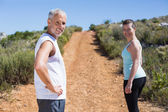 Fit smiling couple jogging up mountain trail — Stock Photo