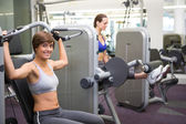 Healthy happy brunette using weights machine for arms — Stock Photo
