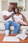 Happy couple relaxing on the couch having coffee — Photo