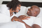 Happy couple laughing together in bed — Stock Photo