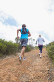 Couple jogging up mountain trail — Stock Photo