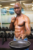 Muscular man holding frying pan in gym — Stock Photo