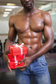 Mid section of a muscular man with gift boxes — ストック写真