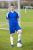 Football player in blue posing with the ball on pitch — Stockfoto