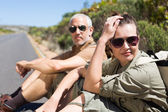 Hiking couple sitting on the side of the road looking at camera — Stock Photo