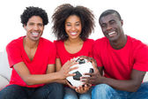 Happy football fans in red holding ball together — Stock Photo
