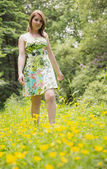 Cute young woman standing in field — Stock Photo