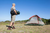 Happy camper walking towards his tent holding sleeping bag — Stock Photo