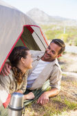 Outdoorsy couple smiling at each other inside their tent — 图库照片