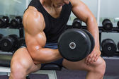 Mid section of muscular man exercising with dumbbell — Stock Photo