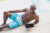 Handsome shirtless man using tablet pc poolside — Stock Photo