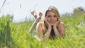 Pretty blonde in sundress lying on grass smiling at camera — Stok fotoğraf