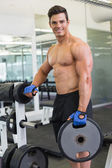 Shirtless muscular man lifting weight in gym — Stock Photo
