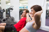 Fit couple doing sit ups on exercise ball — Stock Photo