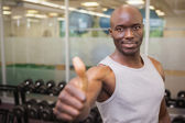 Muscular man giving thumbs up in gym — Stock Photo