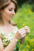 Cute woman holding flower in field — Foto Stock