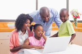 Cute siblings using laptop together with parents — Stock Photo
