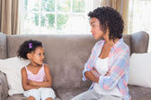 Pretty mother sitting with petulant daughter — Stock Photo