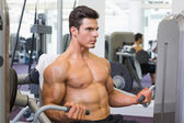 Determined muscular man working on abdominal machine — Stok fotoğraf