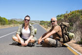 Hitch hiking couple sitting on the side of the road — Stock Photo