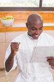 Happy man in bathrobe reading newspaper — Stock Photo