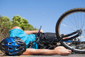 Cyclist lying on the road after an accident — Stock Photo