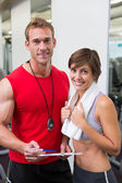 Handsome personal trainer with his client smiling at camera — Stock Photo