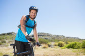 Fit cyclist riding in the countryside smiling at camera — Stock Photo