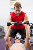 Personal trainer helping client lift dumbbells — Stock fotografie