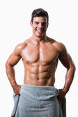 Portrait of a smiling shirtless muscular man wrapped in towel — Foto Stock