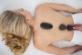 Beautiful blonde enjoying a hot stone massage  — Stock Photo