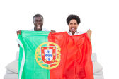 Ecstatic portugal fans sitting on the couch with flag — Stock Photo
