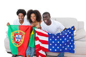 Cheering football fans holding flags on the sofa — Stock Photo