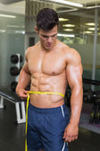 Muscular man measuring waist in gym — Foto de Stock
