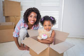 Cute daughter sitting in moving box with mother — Stock Photo