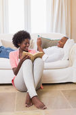 Cute couple relaxing reading book and using smartphone — Stock fotografie