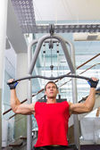 Strong man using weights machine for arms — 图库照片
