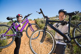 Active couple carrying their bikes on country terrain together — Stock Photo