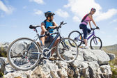 Cyclist couple taking break on rocky peak — Stock Photo
