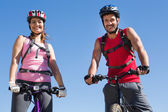 Fit cyclist couple standing at the summit smiling at camera — Stock Photo