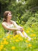 Cute woman relaxing in field — Stock Photo