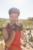 Fit cyclist adjusting helmet strap on country terrain — Stok fotoğraf