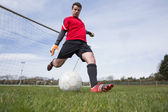 Goalkeeper in red kicking ball away from goal — Stok fotoğraf