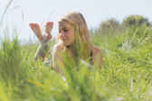 Pretty blonde in sundress lying on grass  — 图库照片