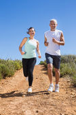 Fit couple running down mountain trail — Stock Photo