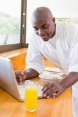 Happy man in bathrobe using laptop at table — Stock Photo