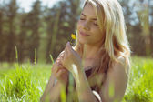 симпатичная блондинка в сарафане проведения желтый цветок — Стоковое фото