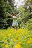Mujer con los brazos extendidos en el campo contra los árboles — Foto de Stock