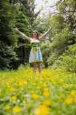 Woman with arms outstretched in field against trees — ストック写真