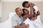 счастливые родители с девочкой на кровати — Стоковое фото